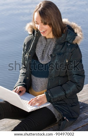 Woman sits on the lake and surf the internet with laptop /Woman with laptop