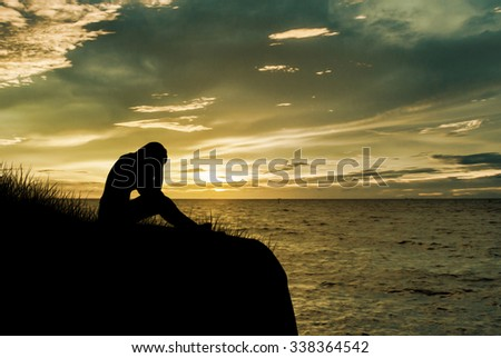 Woman sitting alone and sad depressed with meadow, Silhouette sunset.