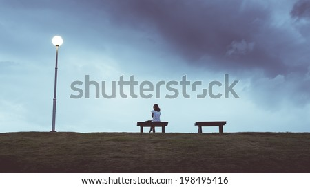 woman sitting alone in a bench  ...
