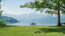 Woman sitting alone on a bench. Attractive girl sits on a wooden bench with amazing view over lake and mountains.Female enjoing a picturesque place. Recreation,peace,mindfulness and relaxation concept
