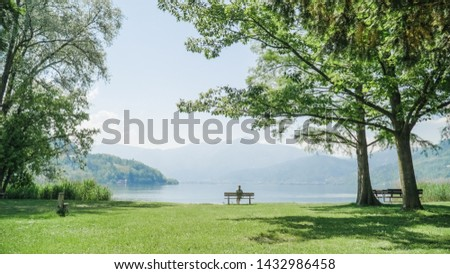 Woman sitting alone on a bench. The attractive girl sits on a wooden bench with amazing view over lake and mountains. Female enjoing a picturesque place. Recreation and relaxation concept.