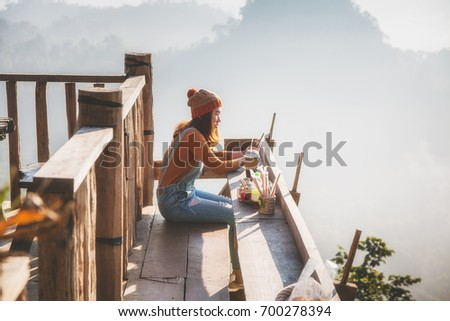 woman sitting and relaxing in Thai restaurant with enjoying sunrise #700278394