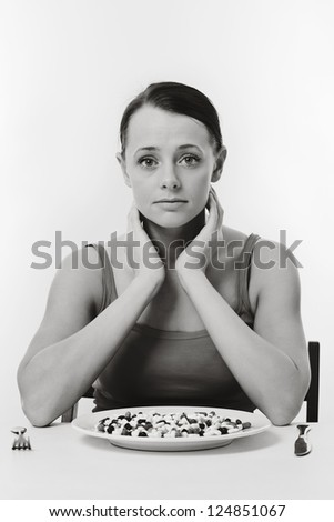 woman sitting at a table about to eat a plate full of pills