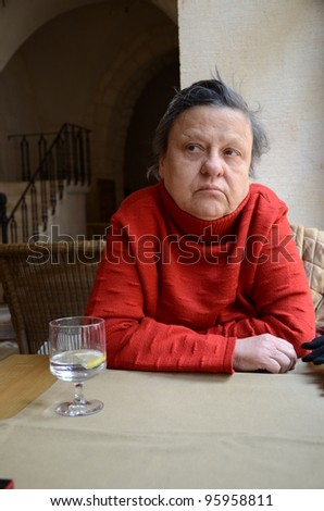 woman sitting at a table where a glass of water