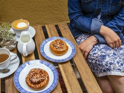 Woman sitting at an outdoor cafe in Gamla Stan, Stockholm, Sweden eating Kanelbulle and drinking coffee.