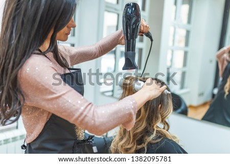 Woman sitting at beauty salon, making hairdo. Beautician drying woman's hair. Young woman talking with her hairstylist during a salon appointment