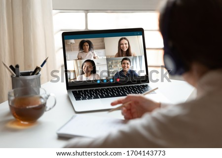 Woman sitting at desk noting writing information studying at home with multiracial students diverse ladies makes video call using video conference application, view over girl shoulder to laptop screen