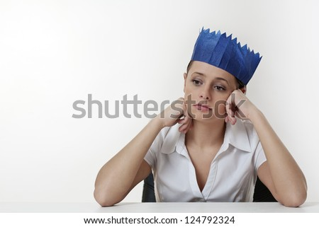 woman sitting at her desk not having a good time wearing a paper hat from a christmas cracker
