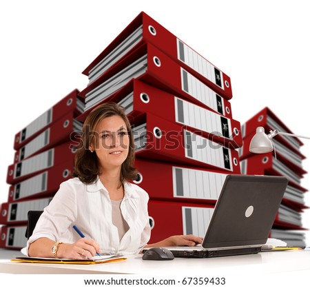 Woman sitting at her desk with piles of ring binders at the background - stock photo
