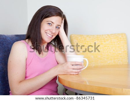 Woman sitting at table drinking coffee alone