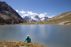 Woman Sitting at the edge of Lac du Goléon in the French Alps with the Mountain Peak La Grave in the Distance