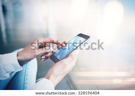 Woman sitting at the floor and touching screen of her smartphone