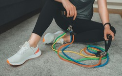 Woman sitting at the floor with resistance bands at home.