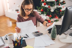 Woman sitting at the office desk and reading letter with christmas tree in the background
