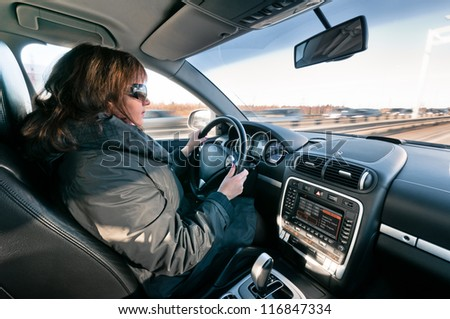 Woman sitting at the steering wheel and driving car