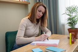 woman sitting at the table and handwriting a note with pen in his personal diary. business planning and record keeping in paper format