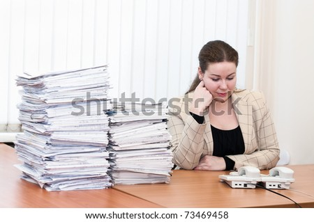 Woman sitting at the table in working place in office room and waiting callback