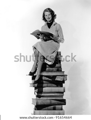 Woman sitting atop pile of books