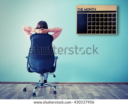 Woman sitting back on the office chair and looking at chalkboard calendar on wall background #430537906