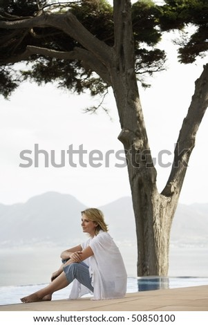 Woman sitting by infinity pool, side view