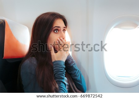 Woman Sitting By the Window on An Airplane Feeling Sick - Aircraft passenger having a bad episode of motion sickness