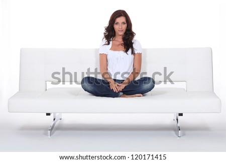 Woman sitting cross legged on a white sofa