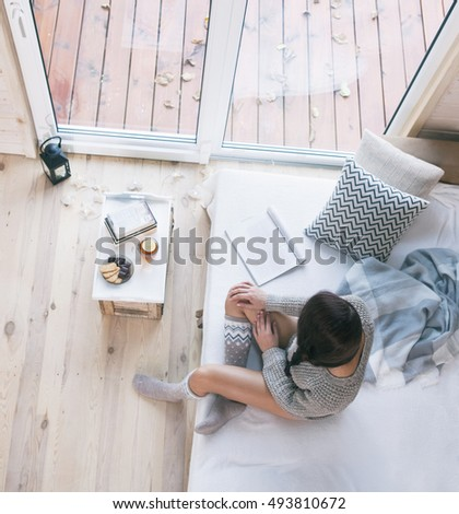Woman sitting home on the bed relaxing enjoying window view. Lantern and christmas lights on the floor, books and sweets on the table.