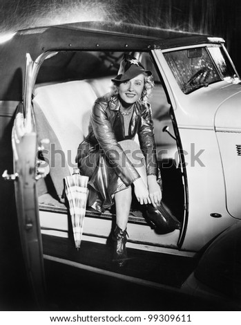 Woman sitting in a car putting on her shoes - stock photo