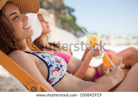 Woman sitting in a deck chair with a friend at her side while holding her cocktail
