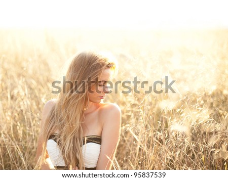 Woman sitting in a field with copy space provided
