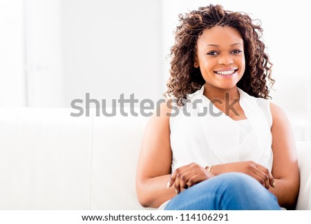 Woman sitting in a sofa at home looking very happy