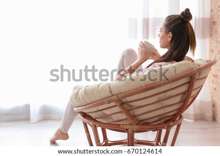 Woman sitting in armchair and drinking coffee #670124614