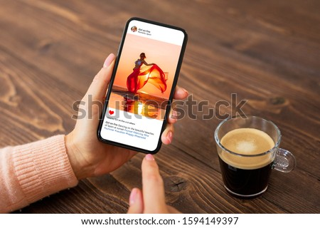 Woman sitting in cafe and viewing someone's photo on mobile phone.