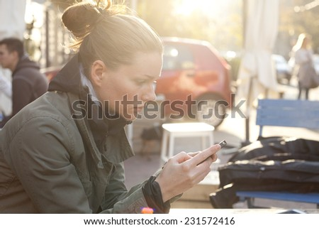 Woman Sitting In Cafe Bar And Using A Mobile Phon