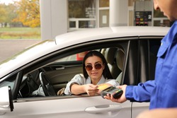 Woman sitting in car and paying with credit card at gas station