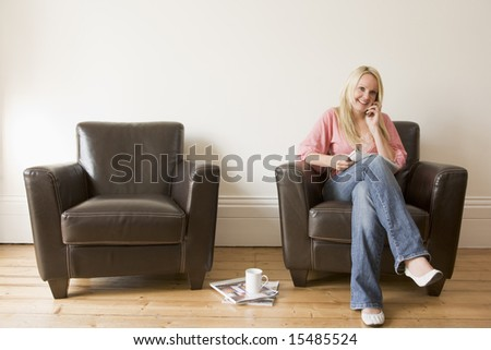 Woman sitting in chair with magazine on cellular phone smiling