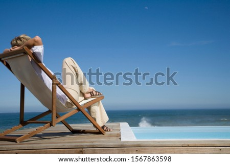 Woman sitting in deck chair near swimming pool