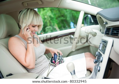 woman sitting in drivers seat of her luxury car talking to mobile phone and searching purse