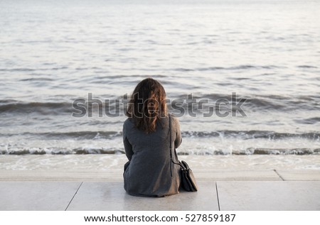 Woman sitting in front of the river, alone. Lisbon. Portugal.
