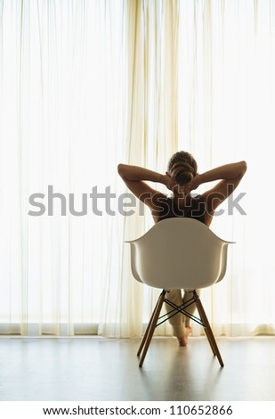 Woman sitting in front of window. Rear view