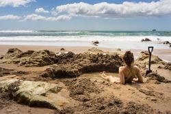 Woman sitting in hot water thermal pool in Hot Water beach in Mercury Bay, Coromandel, New Zealand