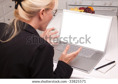Woman Sitting In Kitchen Using Laptop with Blank Screen Ready for Your Own Message. Screen image can easily be replaced using the included clipping path.
