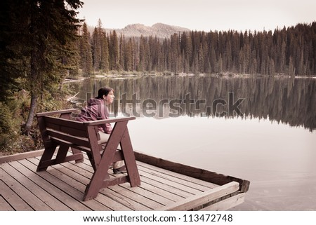 Woman Sitting in Solitude by Lake