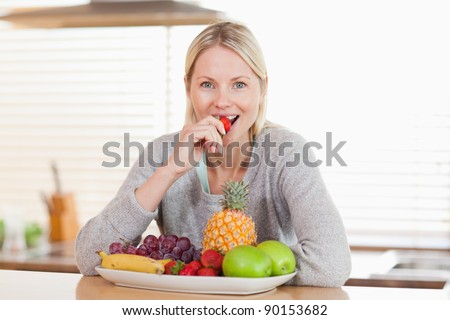 Woman sitting in the kitchen eating a strawberry