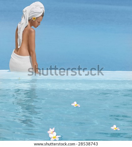 Woman  sitting in  the swimming pool in towel