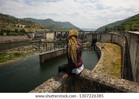 Woman sitting near an old hydroelectric plant