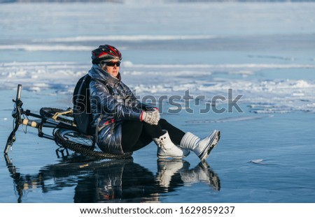 Woman sitting near her bike on ice. The girl cyclist stopped to rest. She sits on the wheel and enjoys the beautiful view of the sunset.