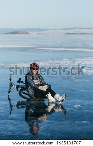 Woman sitting near her bike on ice. The girl cyclist stopped to rest. She sits on the wheel and enjoys the beautiful view of the sunset. The traveler is ride a cycle. Female is riding bike on the ice.