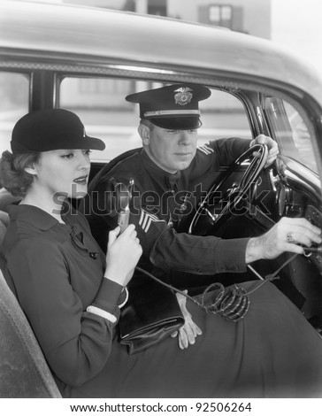 Woman sitting next to a policeman in his car holding a microphone in her hand
