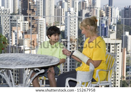 Woman sitting next to boy on balcony overlooking city. Woman and boy talking. Horizontally framed photo.